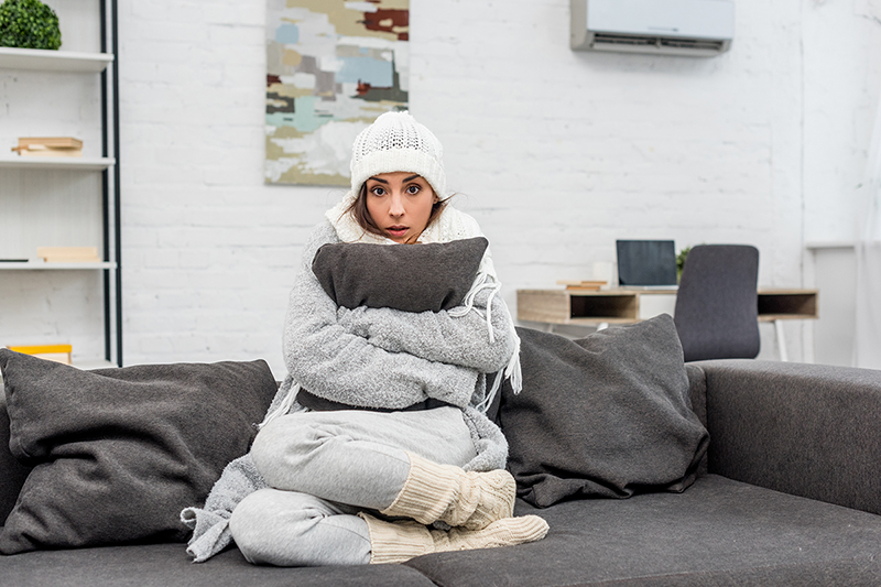 Woman sitting on her bed with lots of layers, heating your home for less