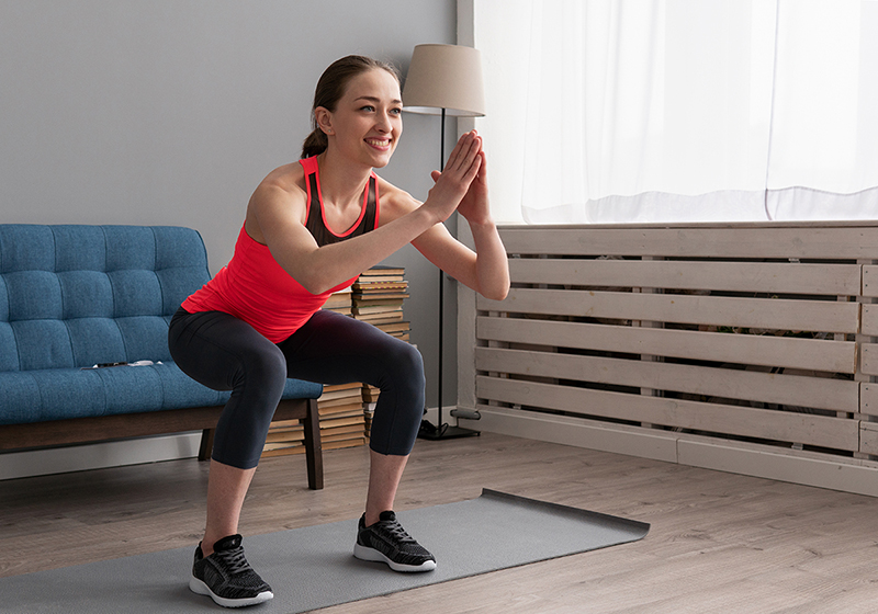Woman doing squats as part of her 30 minute holiday workout