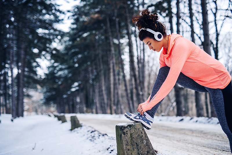 Woman working out during the winter time, staying motivated even though it's cold out