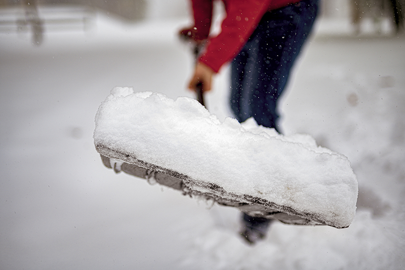 Man shoveling his driveway, how to be prepared for a winter storm