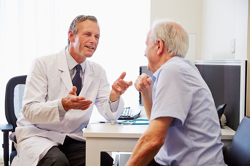Medicare-aged man, visiting with a doctor at his annual wellness visit