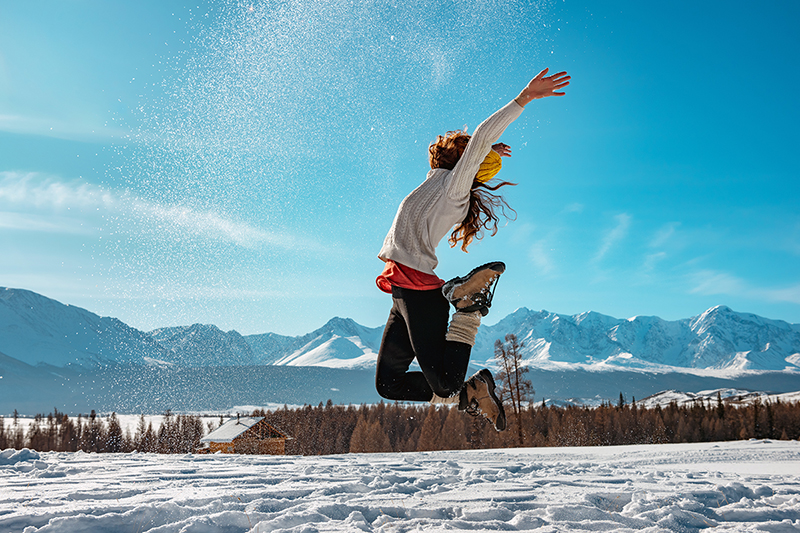 Woman jumping in the snow, enjoying the health benefits of winter