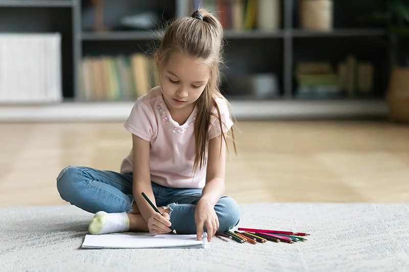 Little girl coloring sitting on the floor, how to keep kids entertained while stuck indoors