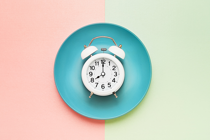 The benefits of intermittent fasting, alarm clock on a plate