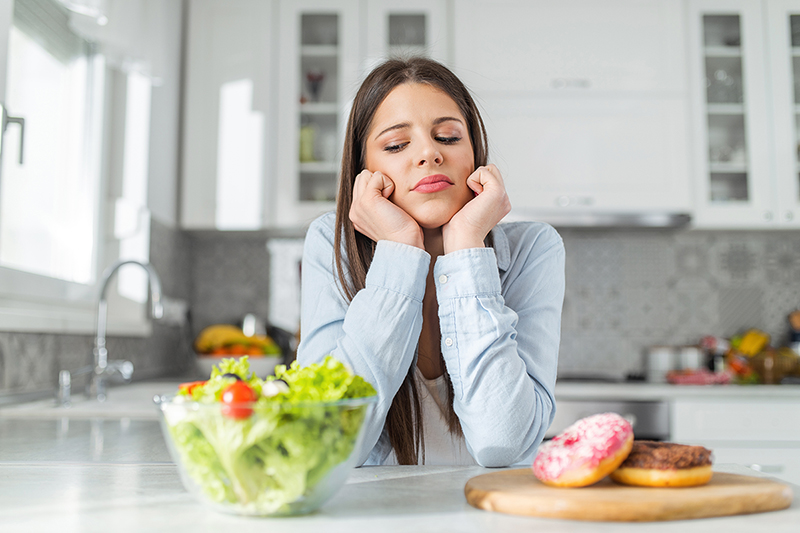 Woman looking at a salad and a donut, diet and weightloss myths