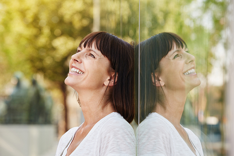 Happy woman in front of a mirror, how to practice self love