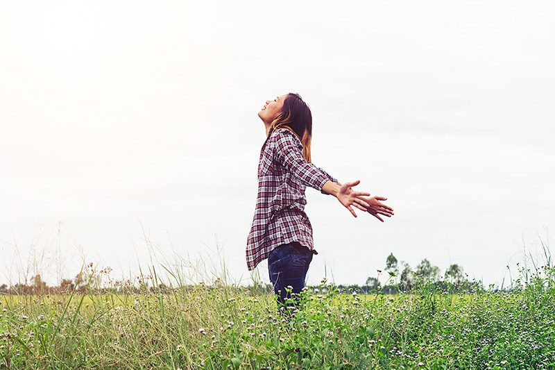 woman in a field, learning how to cope when stress and anxiety hits