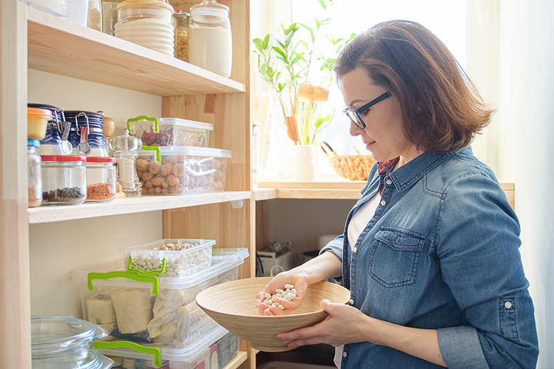 Woman in her pantry using tips for Building Up Food Storage