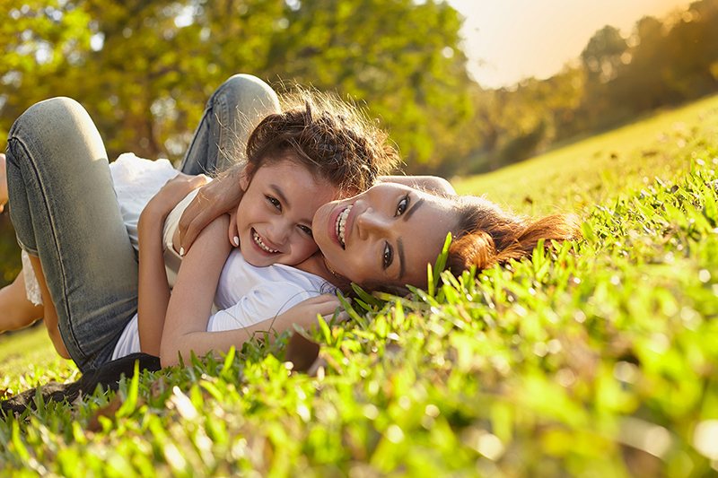 Mom and daughter outside on the grass smiling, how to cultivate happiness and gratitude