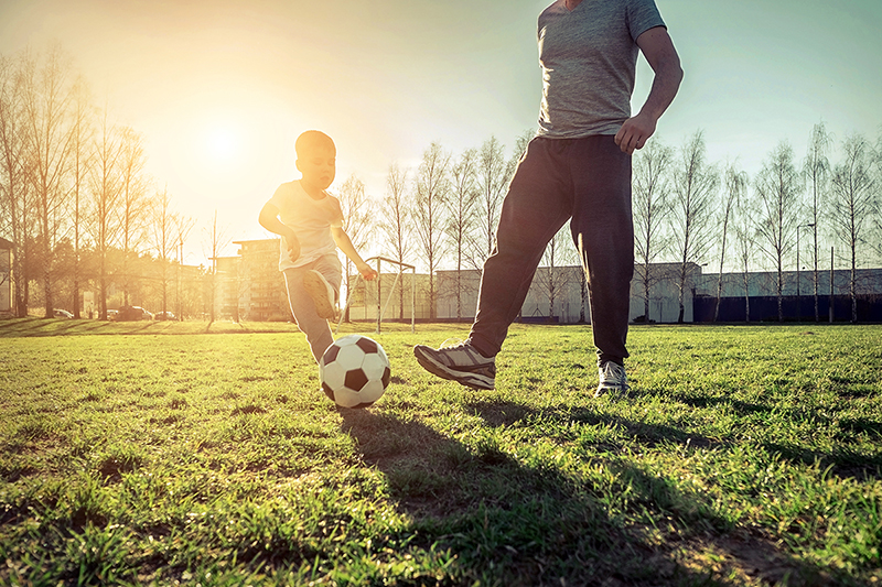 Father and son playing soccer, finding ways to optimize their health