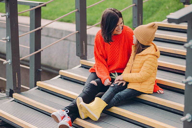 Mother and daughter talking on the steps, how to talk to your kids about COVID-19