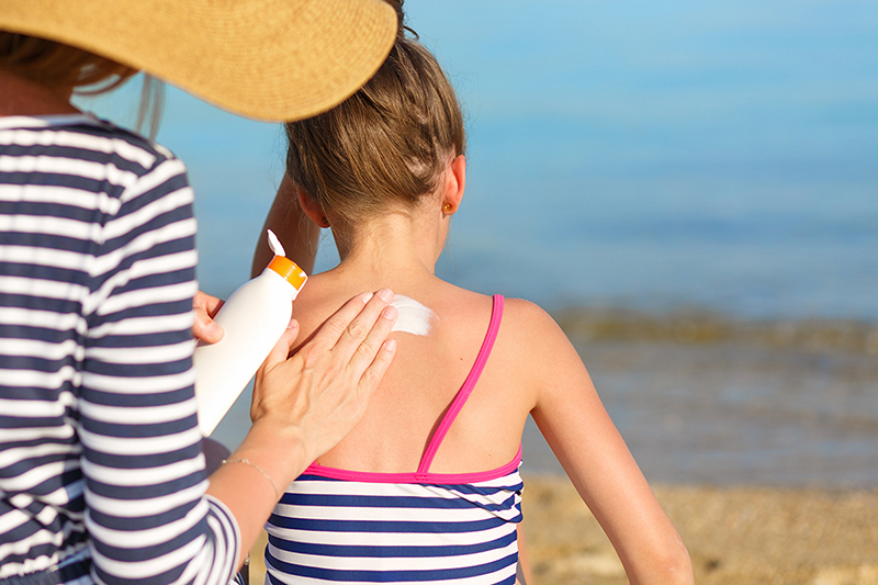 Mom putting sunblock on her daughter, how to choose sunscreen and when to apply