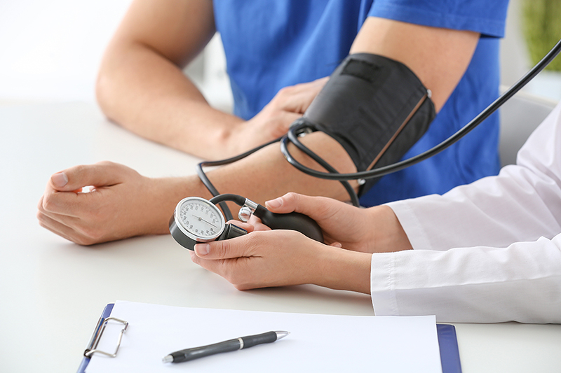 What is high blood pressure? Woman taking someone's blood pressure