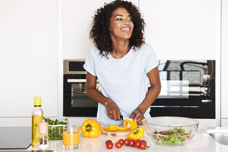 Woman cutting peppers, foods that are good for skin health