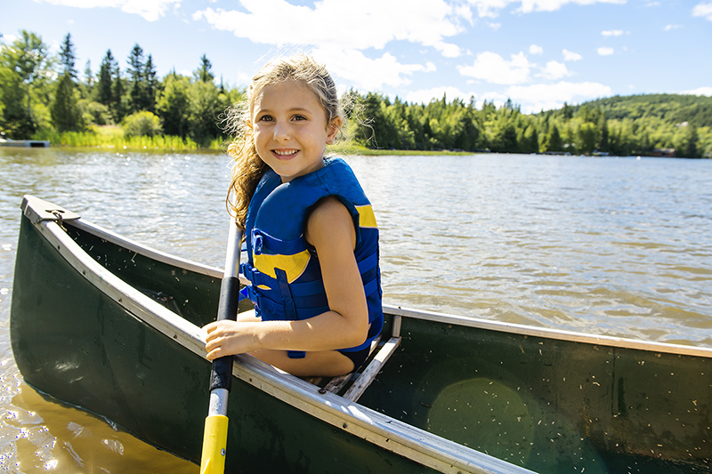 Girl in a canoe on a lake, how to swim safely in natural waters