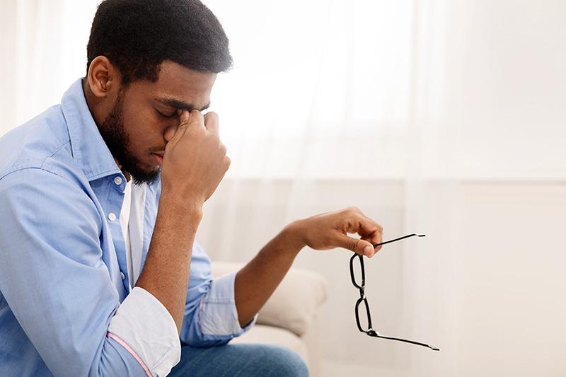 Man with a headache sitting down, what causes headaches?