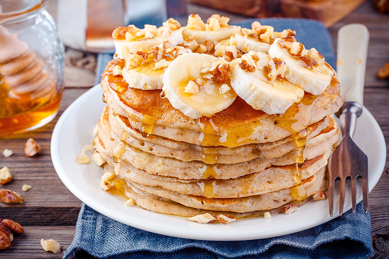 Banana oatmeal blender pancakes on a plate with bananas and nuts, recipe