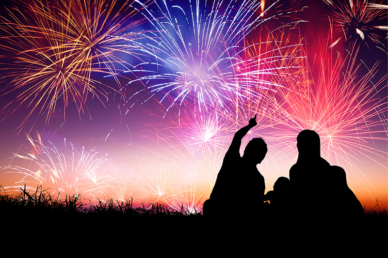 Family outside at night watching fireworks, staying safe while watching fireworks