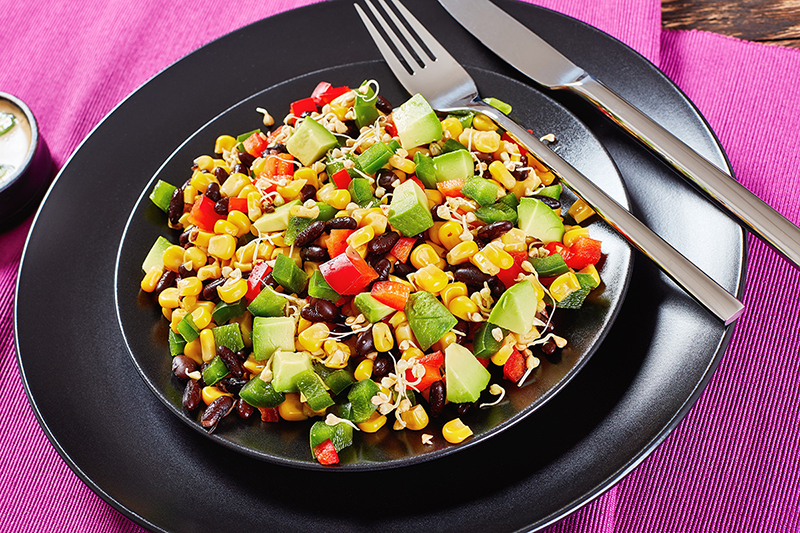 Black bean and corn salad on a plate with a knife and fork, recipe