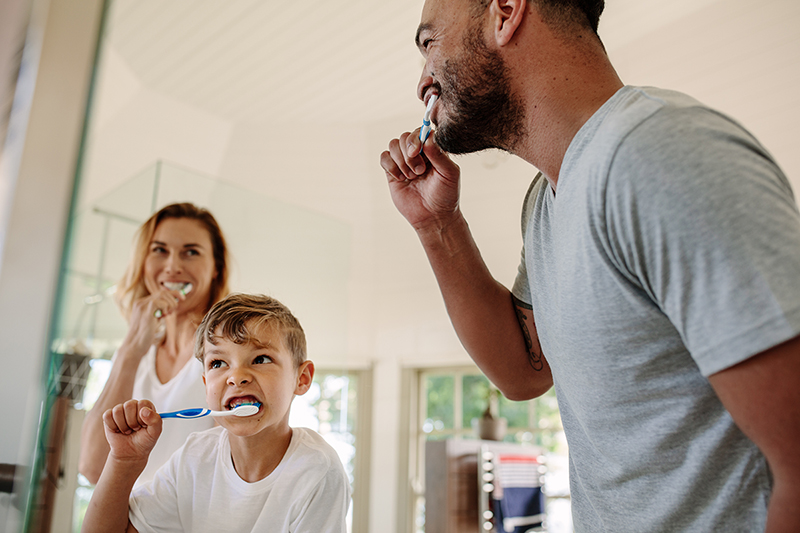 Family in bathroom learning exercises you can do while brushing your teeth