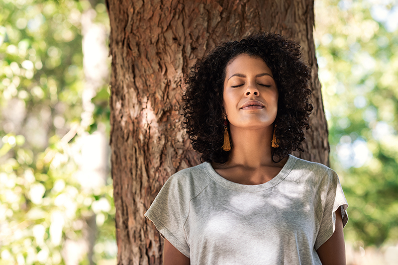 Woman leaning against a tree breathing deep, practicing mindfulness