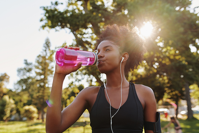 Woman exercising in the summer heat, drinking from a water bottle