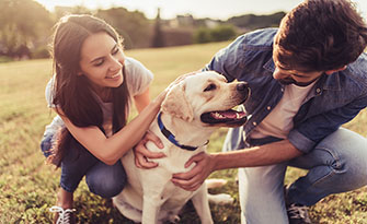 Man and woman outside with their dog, staying positive in hard times sm