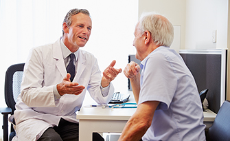 Medicare-aged man, visiting with a doctor at his annual wellness visit sm
