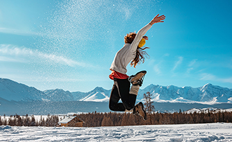 Woman jumping in the snow, enjoying the health benefits of winter sm
