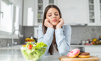 Woman looking at a salad and a donut, diet and weightloss myths sm
