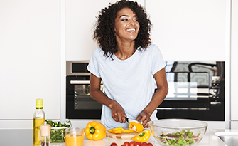 Woman cutting peppers, foods that are good for skin health sm