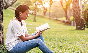 Woman sitting under a tree reading, reasons to take a mental health day sm