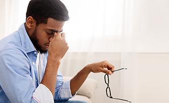 Man with a headache sitting down, what causes headaches? sm