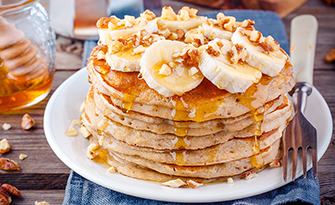 Banana oatmeal blender pancakes on a plate with bananas and nuts, recipe sm