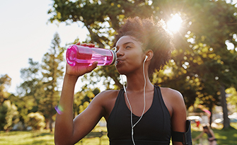 Woman exercising in the summer heat, drinking from a water bottle sm
