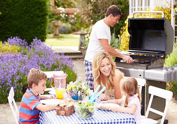 Family outside during the summer having an outdoor barbecue