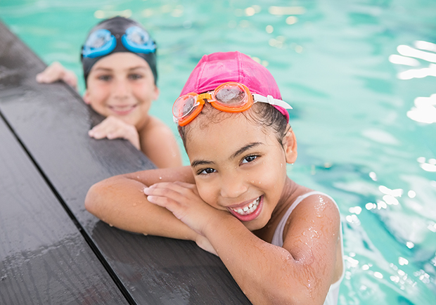 Two children swimming in the pool, water safety tips. Stay safe around water.