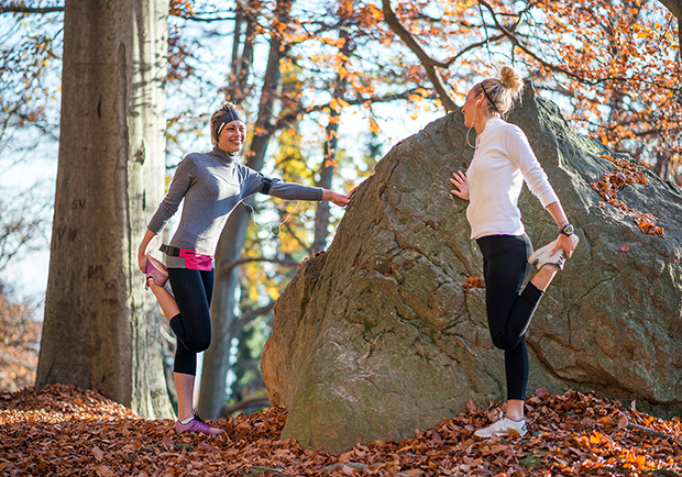 Two runners standing by a rock outside stretching