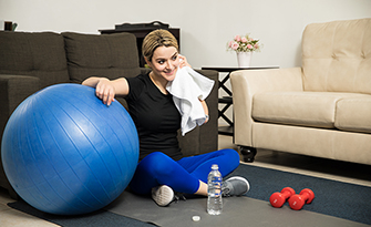 How to sneak in a workoug, woman sitting watching tv while working out.