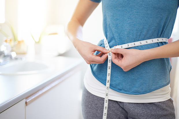 Woman measuring her stomach with a tape measure, 4 ways to decrease belly fat