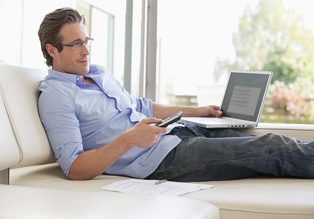 man multitasking while watching TV