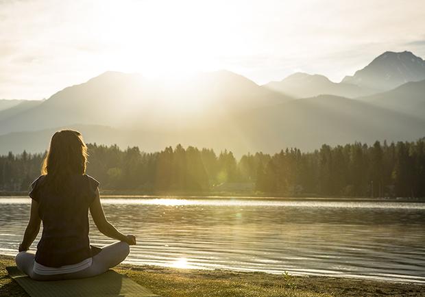 Girl sitting next to lake meditating, the benefits of meditation