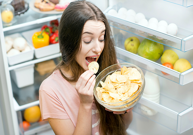 Woman eating potato chips in front of a fridge, weight loss myths debunked