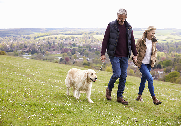 Couple walking with their dog. Get moving, a way to help prevent osteoarthritis