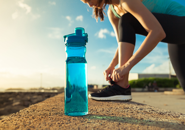 Girl working out, stretching next to a water bottle.
