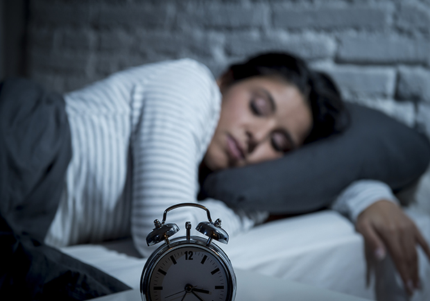 Woman sleeping next to her alarm clock. Myths about sleeping