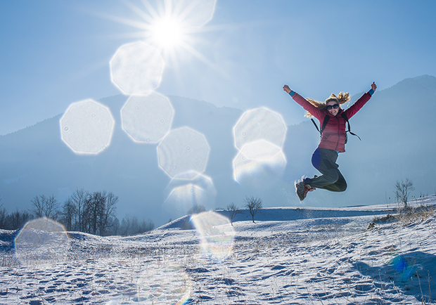 Girl jumping up outside in the snow. Stay motivated with your workouts during winter