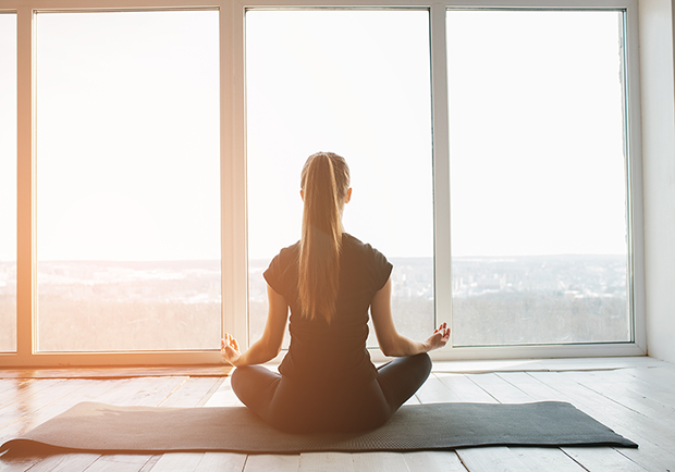 Benefits of yoga, girl doing yoga in front of a window