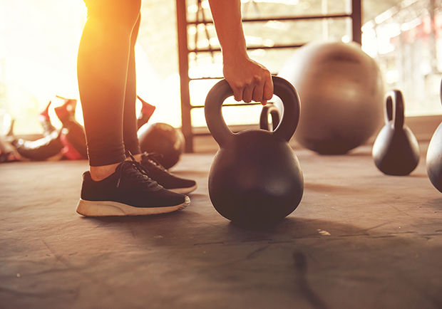 Woman lifting kettleball, reasons to love strength training