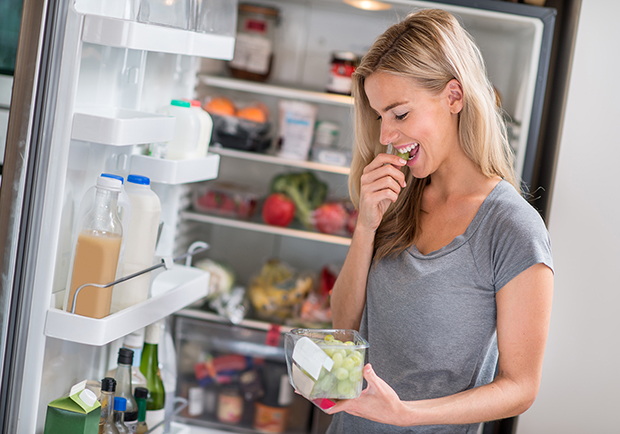 Woman eating grapes in front of a fridge, snacks that are 250 calories or less
